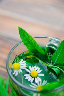 Filiżanka herbaty miętowej z rumiankiem na drewnianym tle. herbata ziołowa z rumiankiem i świeżymi liśćmi mięty na stole.