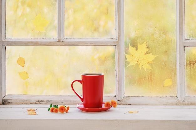 Filiżanka herbaty na białym drewnianym parapecie jesienią