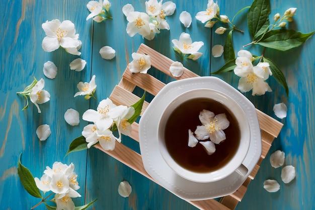 Filiżanka herbaty na drewnianej mini palecie z jaśminowymi kwiatami.