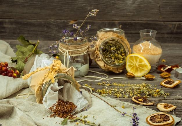 Filiżanka herbaty na drewnianym stole z cytryną i ziołami