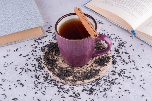 Filiżanka herbaty na marmurowym stole z cynamonem i książkami. zdjęcie wysokiej jakości