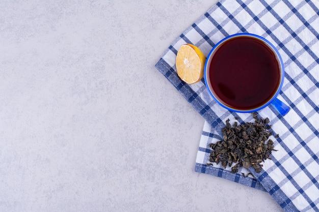 Filiżanka herbaty na obrusie z plasterkiem cytryny i suchą herbatą. zdjęcie wysokiej jakości