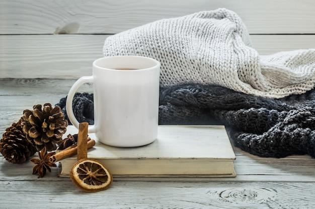 Filiżanka herbaty na pięknym drewnianym stole z zimowym swetrem, stara książka