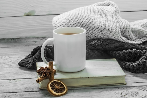 Filiżanka herbaty na pięknym drewnianym tle z zimowym swetrem, stara książka, zima, jesień, szczegół