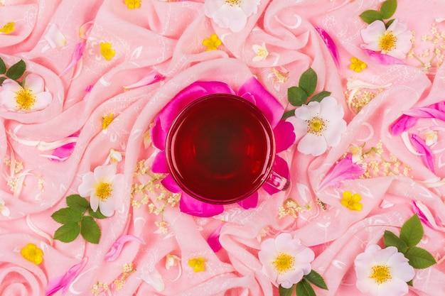 Filiżanka herbaty na tle różowego materiału w różowe kwiaty róży, widok z góry na płasko