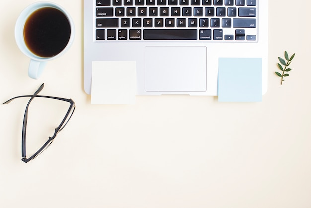 Filiżanka herbaty; okulary i puste samoprzylepne notatnik na laptopie przeciwko beżowym tle