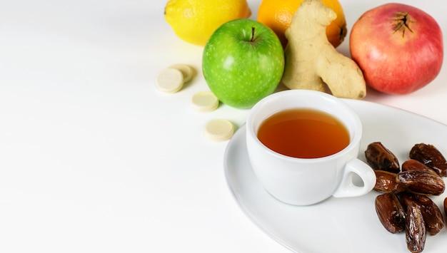 Filiżanka herbaty owocowej, daktyle na białym spodku. grupa tropikalnych owoców cytrusowych, imbir i tabletki multiwitaminy na białym stole. domowy zestaw antywirusowy, wzmacniający system odpornościowy.