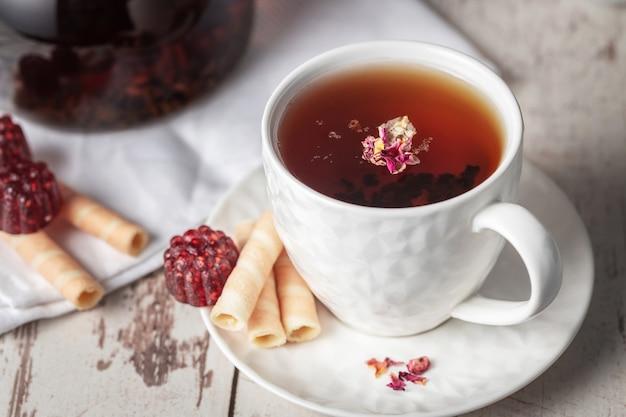 Filiżanka herbaty owocowej z marmoladą w kształcie patyczków truskawek i wafla