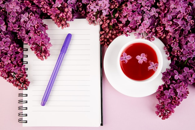 Filiżanka herbaty, pamiętnik i bukiet kwiatów bzu