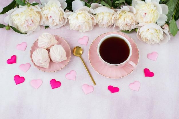 Filiżanka herbaty, pianki, satynowe serca i białe piwonie