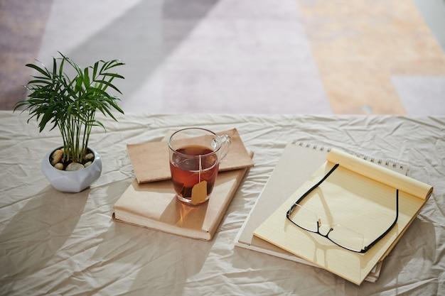 Filiżanka herbaty, planer, szklanki i roślina w garnku na stole przykrytym zmiętym obrusem