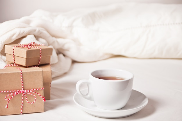 Filiżanka herbaty, pudełka na prezenty świąteczne, dzianinowa kratka na białym