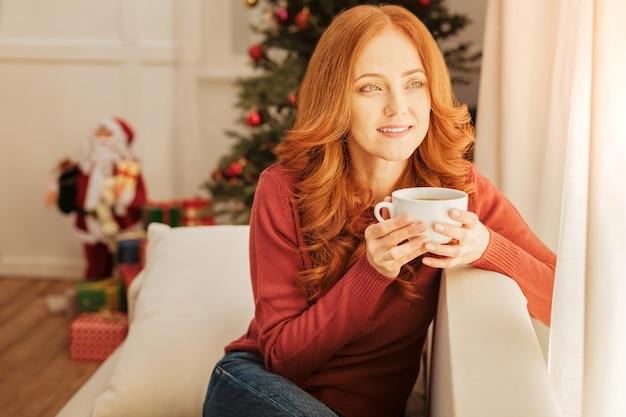 Filiżanka herbaty rozwiązuje wszystko. zrelaksowana ruda dojrzała pani uśmiechnięta siedząc na kanapie i rozgrzewająca się przy filiżance aromatycznej herbaty.