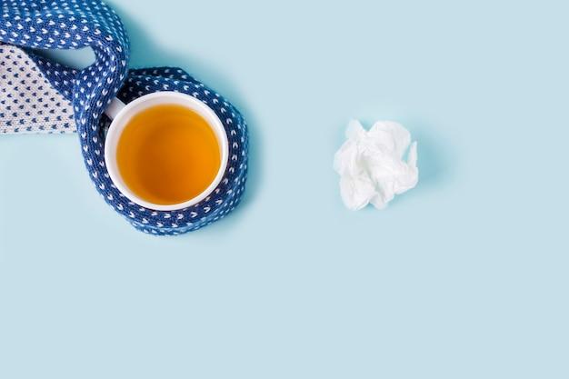 Filiżanka herbaty rumiankowej i zmięty papier chusteczki na niebieskim tle. choroby sezonowe i leczenie przeziębień, grypy, upałów. zapobieganie wirusom. skopiuj miejsce na tekst