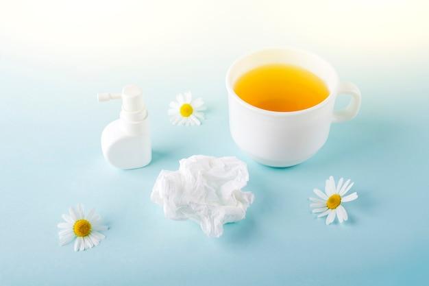 Filiżanka herbaty rumiankowej, spray na katar i zmięty papier chusteczki na niebieskim tle. choroby sezonowe i leczenie przeziębień, grypy, upałów. zapobieganie wirusom. skopiuj miejsce na tekst.
