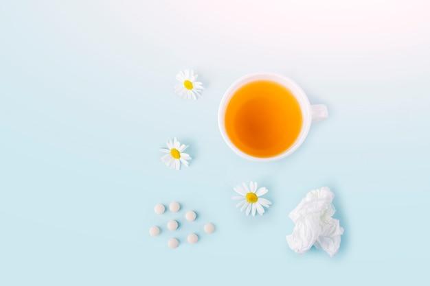 Filiżanka herbaty rumiankowej, zmięty papier chusteczki i tabletki na niebieskim tle. choroby sezonowe i leczenie przeziębień, grypy, upałów. zapobieganie wirusom. skopiuj miejsce na tekst.