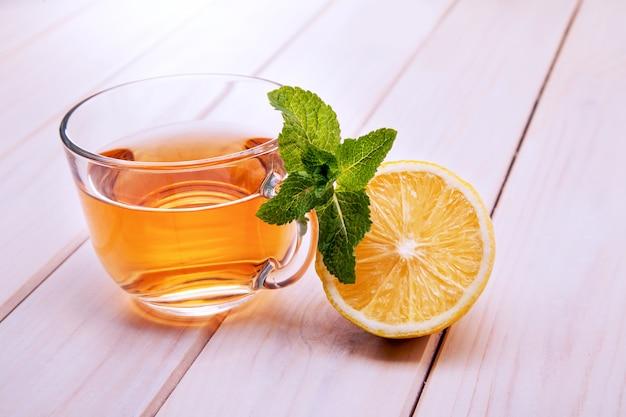 Filiżanka herbaty, szklany czajniczek, mięta i cytryna na drewnianym stole