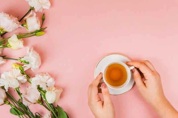 Filiżanka herbaty trzymając się za ręce