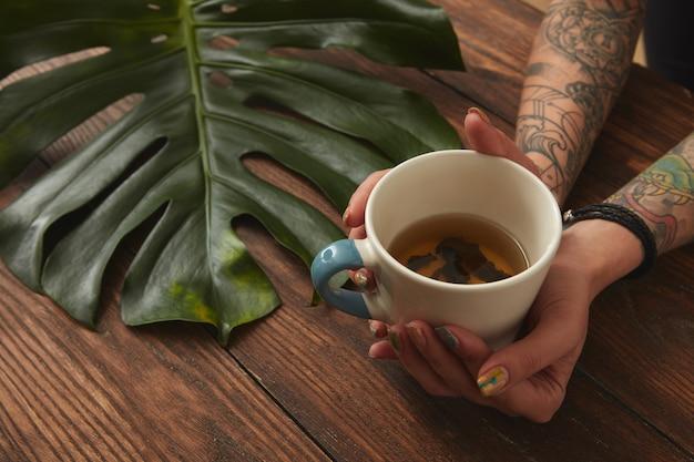 Filiżanka herbaty w kobiecych rękach na drewnianym tle z zielonym liściem