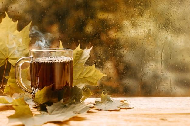 Filiżanka herbaty w liściach deszczowe okno nastrój jesienny dzień