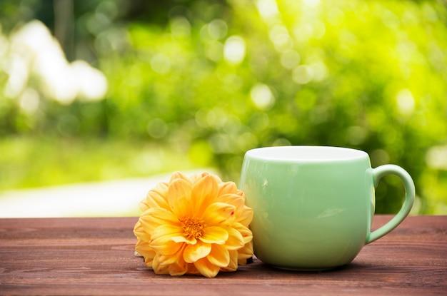 Filiżanka herbaty w pogodnym ogródzie na drewnianym stole. okrągły kubek z kwiatową herbatą i aster na tle letniego ogrodu. zielone tło zamazane pole. skopiuj miejsce