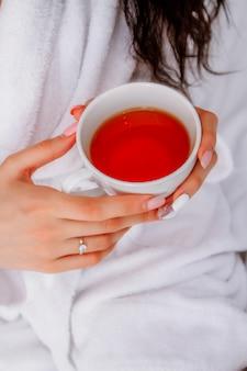 Filiżanka herbaty w rękach dziewczynki. rano śniadanie w łóżku. kubek do herbaty ze stopami w łóżku.