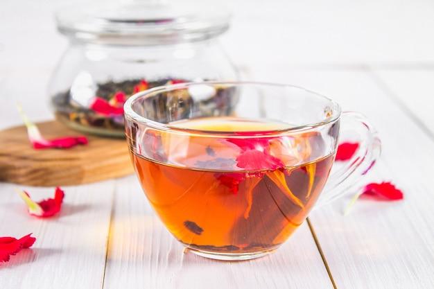 Filiżanka herbaty, w tle banku z czarną ziołową herbatą kwiatową na białym drewnianym stole.