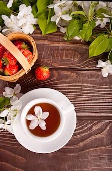 Filiżanka herbaty z białymi kwiatami jabłoni na drewnianym stole