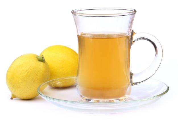 Filiżanka herbaty z całą cytryną na białym tle