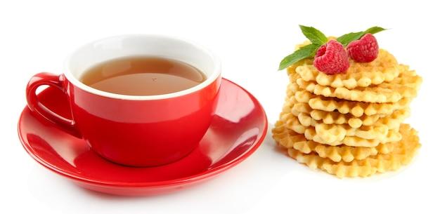 Filiżanka herbaty z ciasteczkami i malinami na białym tle