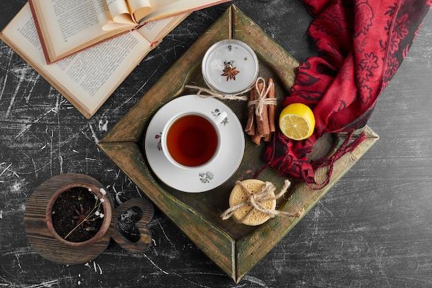Filiżanka herbaty z ciasteczkami i przyprawami.