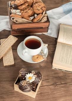 Filiżanka herbaty z ciasteczkami owsianymi i krakersami.