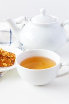 Filiżanka herbaty z ciastkami nad lilym drewnianym tłem