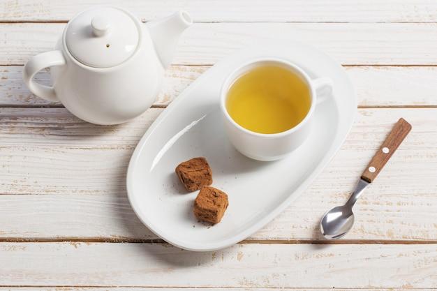 Filiżanka herbaty z cukierkami czekoladowymi na drewnianym stole