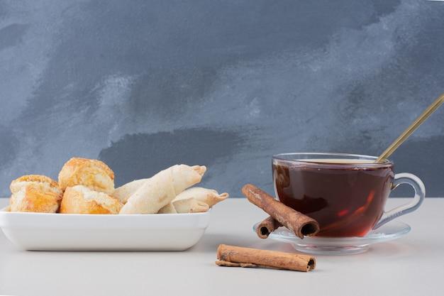 Filiżanka herbaty z cynamonami i ciasteczkami na białym stole.