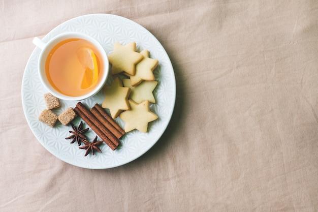 Filiżanka herbaty z cytryną i ciastkami, miód i cynamon, anyż na kocu