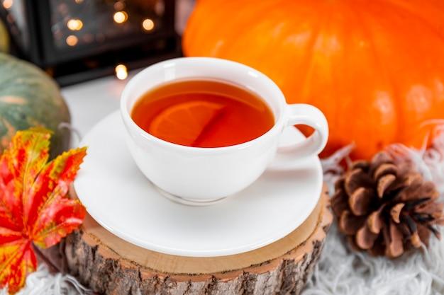 Filiżanka herbaty z cytryną, jesiennymi liśćmi i dynią z bliska. koncepcja przytulnej jesieni w domu. zdjęcie wysokiej jakości