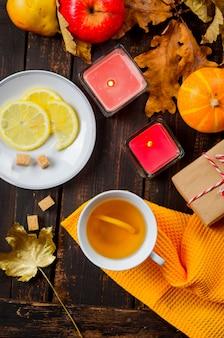 Filiżanka herbaty z cytryną na drewnianym ciemnym stole z jesiennymi liśćmi, dynie. jesienny wystrój, jesienny nastrój, jesienna martwa natura. koncepcja sezonu jesiennego. święto dziękczynienia i święto halloween. układanie płaskie, kopiowanie przestrzeni
