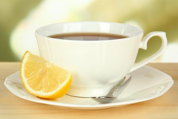Filiżanka herbaty z cytryną na stole na drewnianym stole