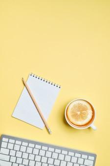 Filiżanka herbaty z cytryną obok klawiatury, notatnik i ołówek na żółtym tle. widok z góry.