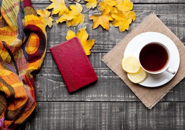 Filiżanka herbaty z cytryną z szalikiem i jesienne liście na powierzchni drewnianych