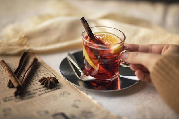 Filiżanka herbaty z cytrynowymi laskami cynamonu i goździkami