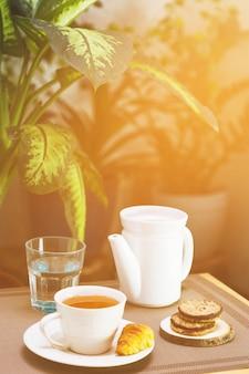 Filiżanka herbaty z czajnikiem i elementami śniadaniowymi