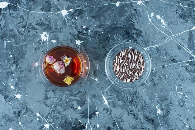 Filiżanka herbaty z czekoladowym ciasteczkiem na niebieskim stole.