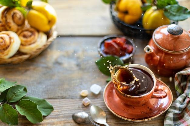 Filiżanka herbaty z domowej roboty pigwa dżemem na starym drewnianym tle. świeże owoce i pigwa liście na tle. poziome zdjęcie. skopiuj miejsce miejsce na tekst. widok z góry