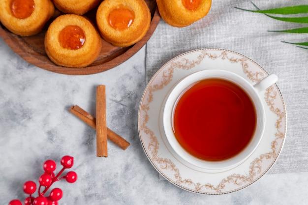 Filiżanka herbaty z domowymi ciasteczkami z dżemem morelowym.