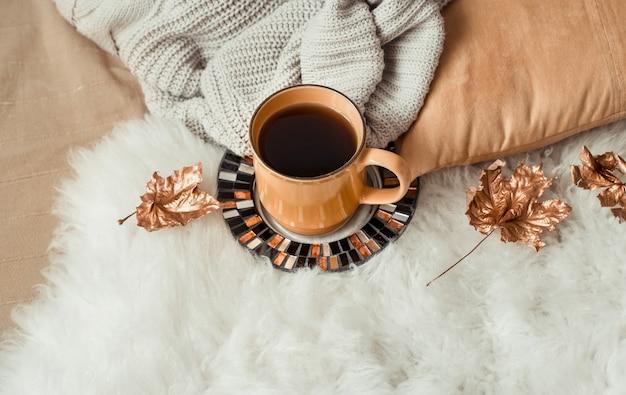 Filiżanka herbaty z jesiennymi liśćmi i swetrem