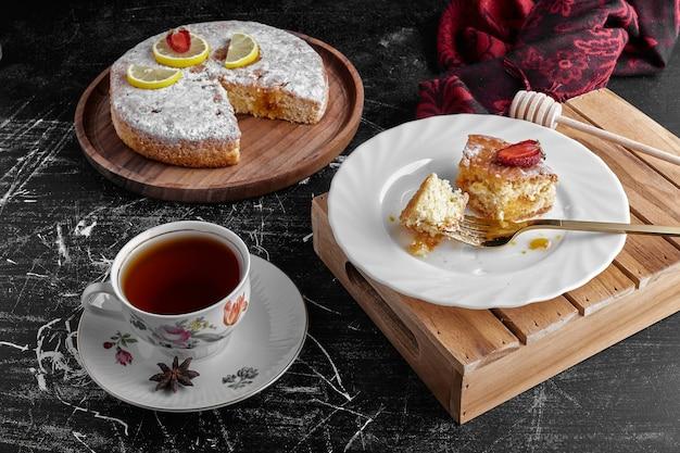Filiżanka herbaty z kawałkami ciasta marchewkowego.
