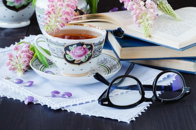 Filiżanka herbaty z książkami i kwiatami na drewnianym stole