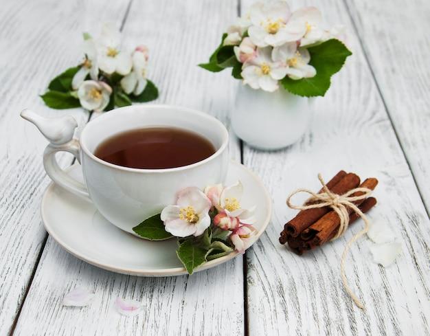 Filiżanka herbaty z kwiatami jabłoni